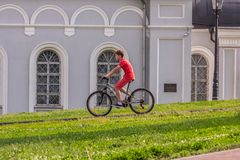A boy biking down the hill in the park. Active lifestyle of children in the summer.