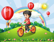 A boy biking at the hilltop with a rainbow and floating balloons Royalty Free Stock Images