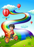 A boy biking at the hilltop with a rainbow Royalty Free Stock Photo