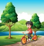 A boy biking at the riverbank Stock Photo