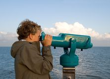 Boy at binoculars. Boy (8) looking at the sea through naval binoculars in the evening Stock Images