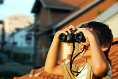 Boy with binoculars. Teen boy looking through black binoculars outdoor portrait Royalty Free Stock Photo