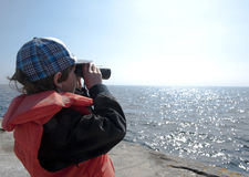 Boy with binoculars. Boy looking at the horizon with a pair of binoculars Stock Photography