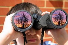 Boy with binoculars. Boy using his binoculars, focus on sunset scene reflected in the object lenses Royalty Free Stock Photography