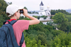 Boy with binoculars and backpack. Boy with backpack looks through binoculars stock photo