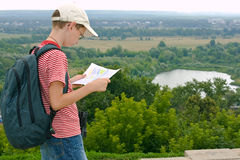Boy with binoculars and backpacklooks at the map. On a hike stock image