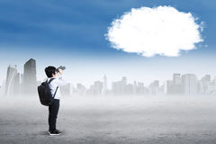 Boy with binoculars looking at cloud. Little boy carrying bag and using binoculars to look at empty cloud on the sky Royalty Free Stock Images