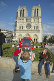 Boy at binoculars looking at Notre Dame Cathedral, Paris, France Royalty Free Stock Photography