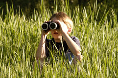Boy with binoculars from side stock image