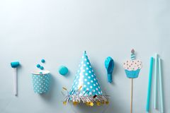 Boy birthday decorations. Blue table setting from above with muffins, drinks and party gadgets. Background layout with free text. Boy birthday decorations. Blue stock image