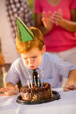 Boy on birthday party blowing a candles. On cake Royalty Free Stock Photos