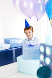 Boy at birthday party surrounded by presents Stock Images