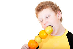 Boy bites the apple skewers. On a white background Royalty Free Stock Photography