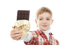 Boy biting bar of chocolate Royalty Free Stock Photography