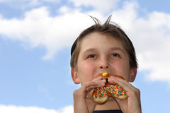 Boy biting into donut Royalty Free Stock Photos