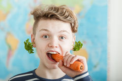 Boy Biting into Large Carrot in Classroom Stock Images