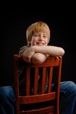 Boy on black background. Boy sitting on chair for studio portrait Royalty Free Stock Images