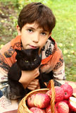 Boy with black cat and red apples close up portrait Stock Image
