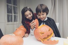 A boy in a black cloak made a beautiful, scary pumpkin for Halloween, a girl in a red dress is ecstatic Stock Photo