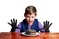 Boy in black gloves emotionally eating a burger stock image
