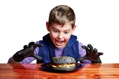 Boy in black gloves emotionally eating a burger royalty free stock images
