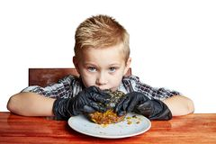 Boy in black gloves emotionally eating a burger stock photo