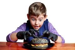 Boy in black gloves emotionally eating a burger stock images