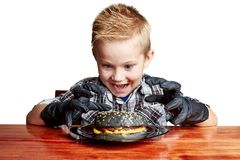 Boy in black gloves emotionally eating a burger stock photography
