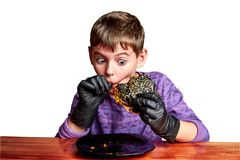 Boy in black gloves emotionally eating a burger royalty free stock photography