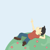 Boy with black hair lying on the ground and looking up at the sky, pointing at something interesting. Royalty Free Stock Images