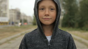 A boy in a black hood on the street. The child in a black jumper with a hood on the street stock video footage