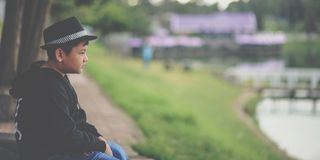 Boy in Black Jacket and Black Fedora Hat Sitting Near Body of Water Stock Photography