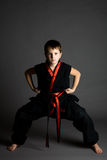Boy in black kimono. Serious young boy in a black kimono with red trim in a crouched pose, on a grey background Stock Photos