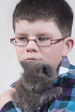 Boy with black kitten. Boy with glasses holding a black cat Royalty Free Stock Photography