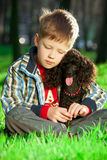 The boy with black poodle Stock Images