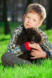 The boy with black poodle Stock Photography