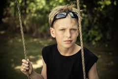 Boy in black shirt sits alone on rope swing Stock Photo