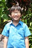 Boy with black spectacle. Smiling boy in blue shirt wearing black-frame spectacle Stock Photo