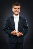 Boy in a black suit jacket corrects Royalty Free Stock Photography