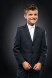 Boy in a black suit jacket corrects. Cheerful boy in a black suit jacket corrects Stock Photo
