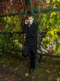 Boy in black suit said by telephone amid foliage Royalty Free Stock Images