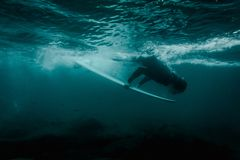 Boy in the black swimsuit flowing down holding a surf board dive under the wave royalty free stock images