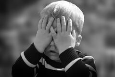 Boy in Black and White Sweater Covering His Face With His Tow Hand Stock Photos