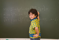 The boy at blackboard. The little boy at blackboard in school Royalty Free Stock Photography