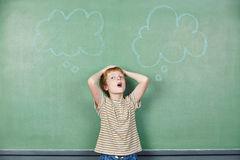 Boy at blackboard with thought Royalty Free Stock Photography
