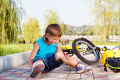 Boy with a bleeding injury. Crying boy with a bleeding injury sitting beside the bike that he has fallen from Stock Photography