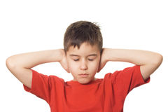 Boy blocking his ears. Boy with closed eyes holding both hands on his ears to prevent him from hearing royalty free stock photos