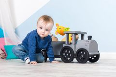 Boy blond in a blue sweater sits on a wooden floor. One year old baby playing with wooden toys.  train made of wood, with girafe. Inside, blue wall at stock images