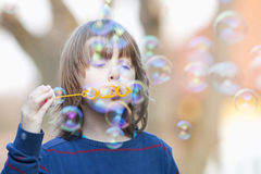 Boy with Blond Hair Blowing Bubbles Royalty Free Stock Photo