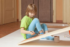 Boy with Blond Hair Painting a Board Stock Photo